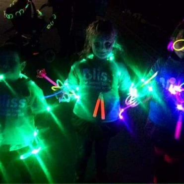 Darkness with 3 people wearing Bliss t-shirts lit up with glow sticks and lights
