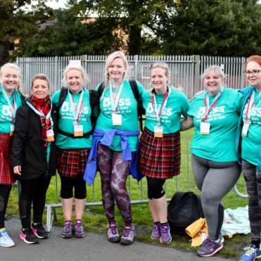 Seven women standing smiling in Bliss t-shirts, some are wearing kilts