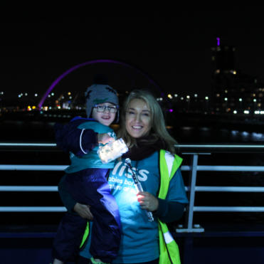 Mum and son on bridge with torch in dark
