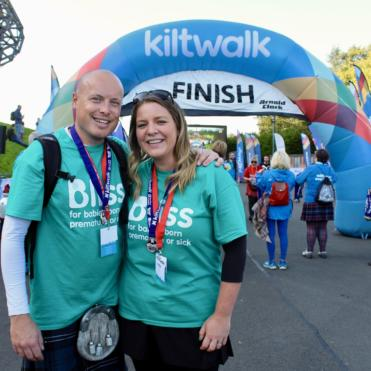 Man and woman at finish line of Kiltwalk wearing Bliss t-shirts