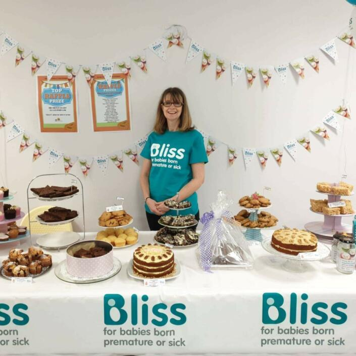 Lady wearing Bliss t-shirt standing behind a table of cakes and bunting and balloons behind, and table decorated with Bliss logo