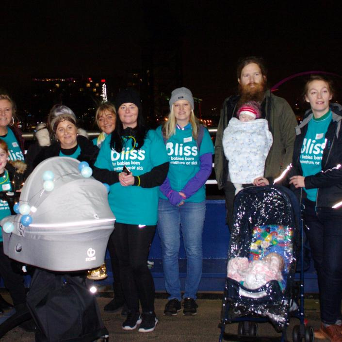 Group of children and adults with 2 prams wearing Bliss t-shirts at night in Glasgow