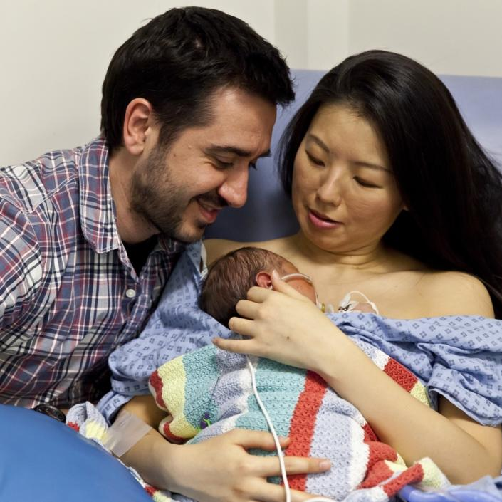 Mum and dad holding baby with mum sitting in hospital chair cuddling baby on chest and dad looking at baby