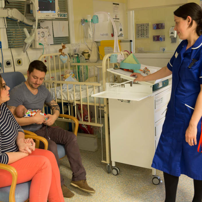 A nurse on the neonatal unit supporting two parents sitting down on chairs with Father holding and looking at his baby,