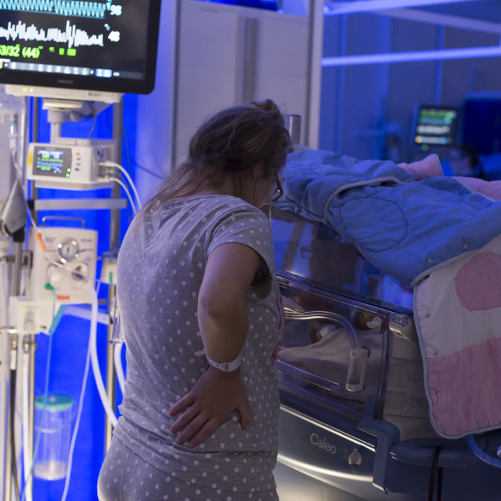 Mum standing by incubator in low light, looking at her baby and away from the camera