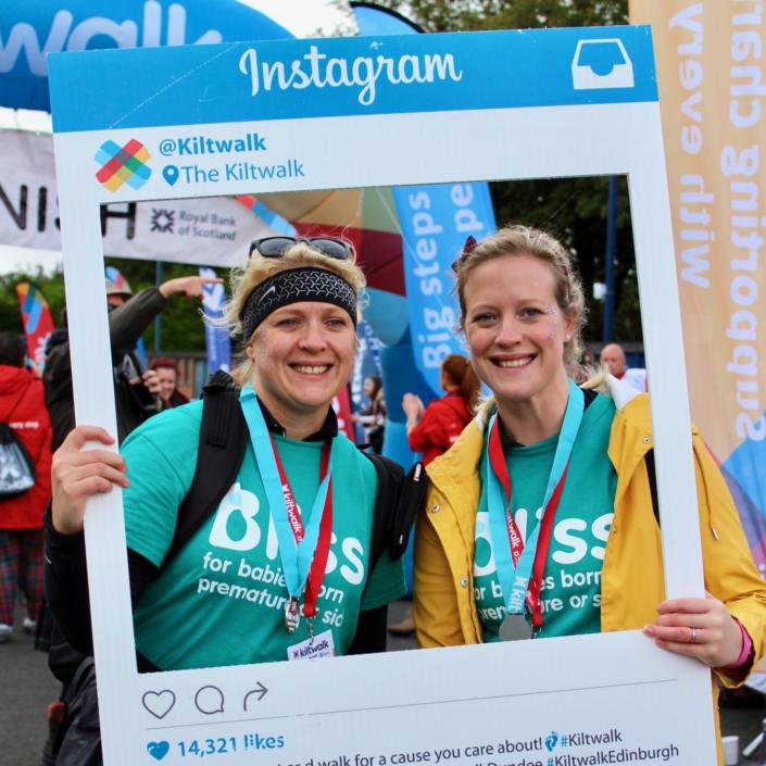 two women in Bliss t-shirts at Kiltwalk finish line holding a instagram style photo frame