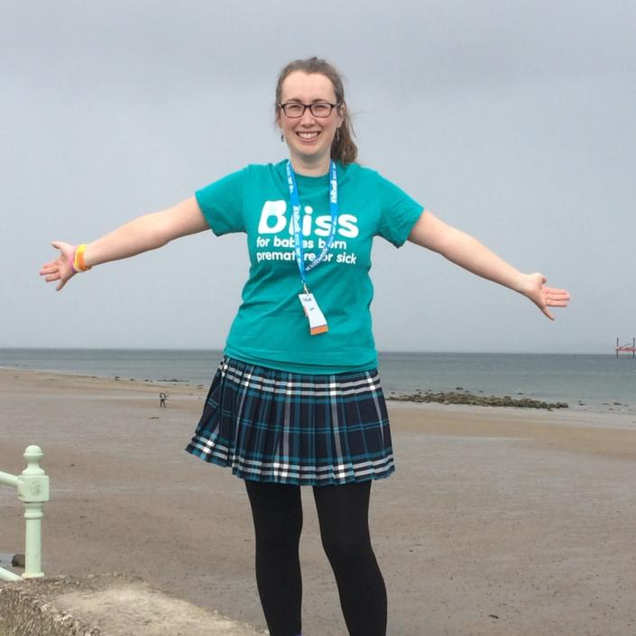 Woman wearing bliss t-shirt and kiltwalk with Portobello Beach behind her.