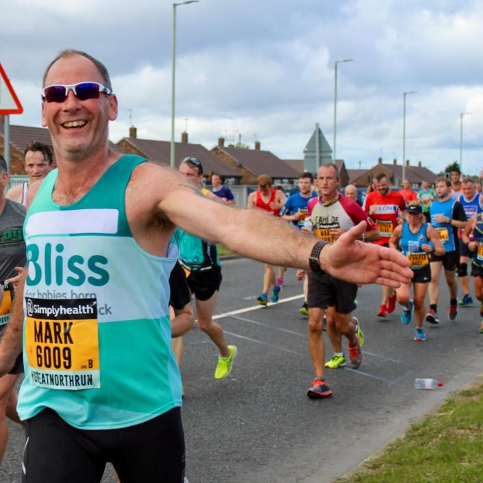 Man running Great North Run reaching out to give high five.