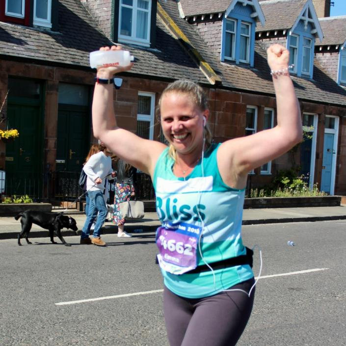 woman in Bliss running vest cheering in sunshine