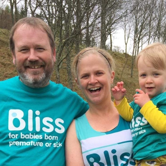 A man in Bliss t-shirt standing next to a female runner in Bliss running vest holding toddler wearing Bliss t-shirt.