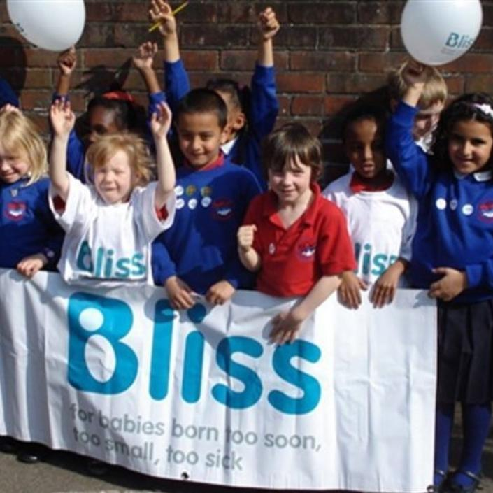 Primary school aged children with balloons and Bliss banner