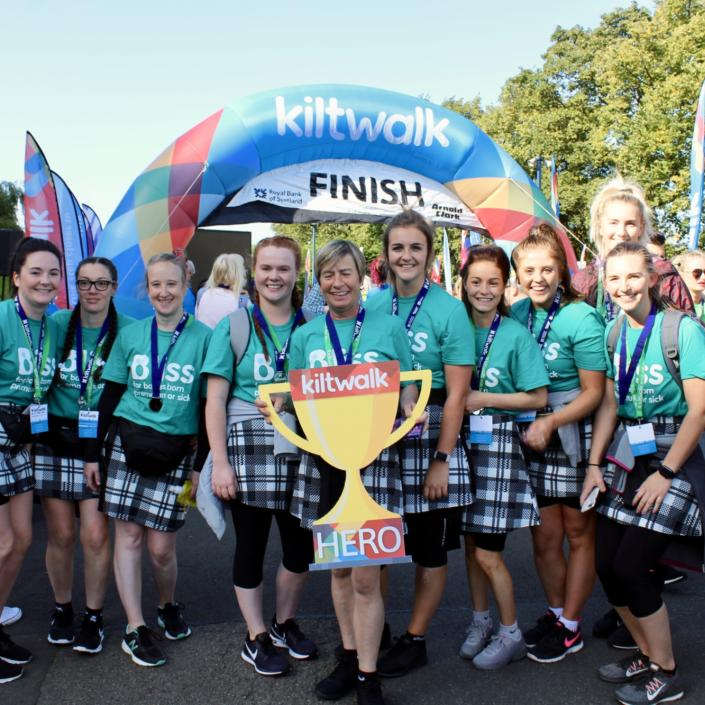 Group of women wearing kilts and bliss t-shirts at Kiltwalk finish line holding foamboard cut-out Kiltwalk hero trophy