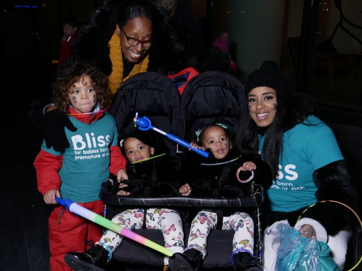 2 Adults, young child and 2 toddlers in a twin buggy wrapped up warm in darkness