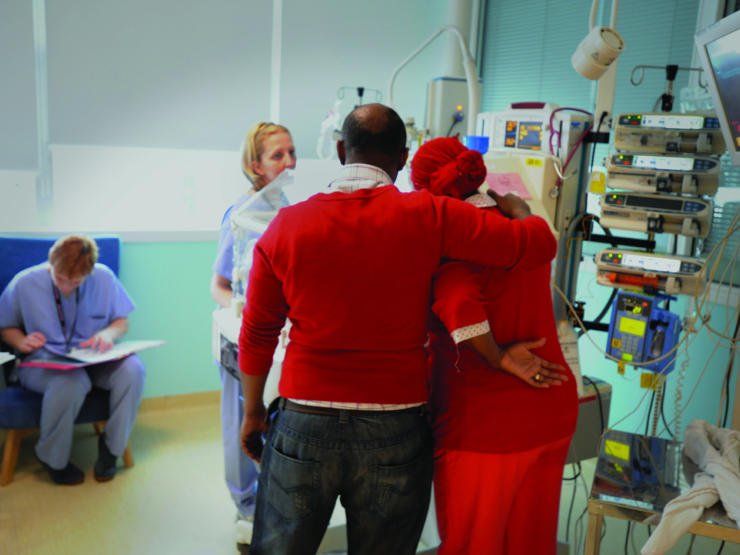 Facing away from the camera, Dad puts arm around Mum in a caring way whilst looking at baby in an incubator surrounded by two health professionals