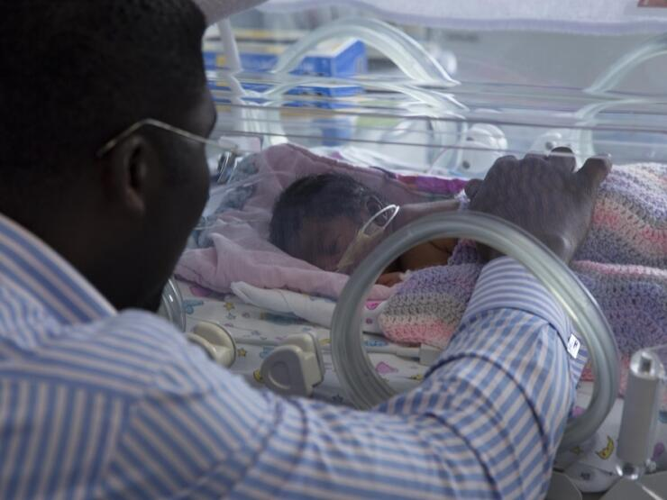 Dad with hand on baby in incubator with baby lying on front asleep and blanket over