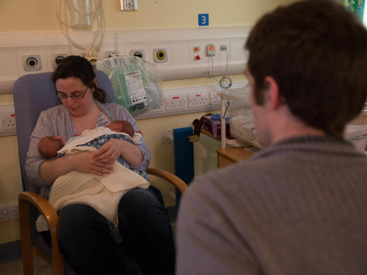 Dad in foreground looking away from camera towards Mum who is sitting holding and looking at her twins in her arms