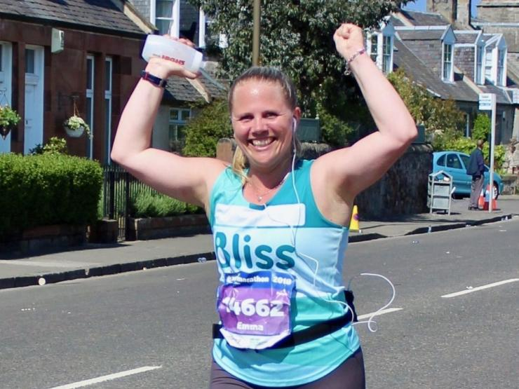 Woman cheering as she runs in Bliss vest