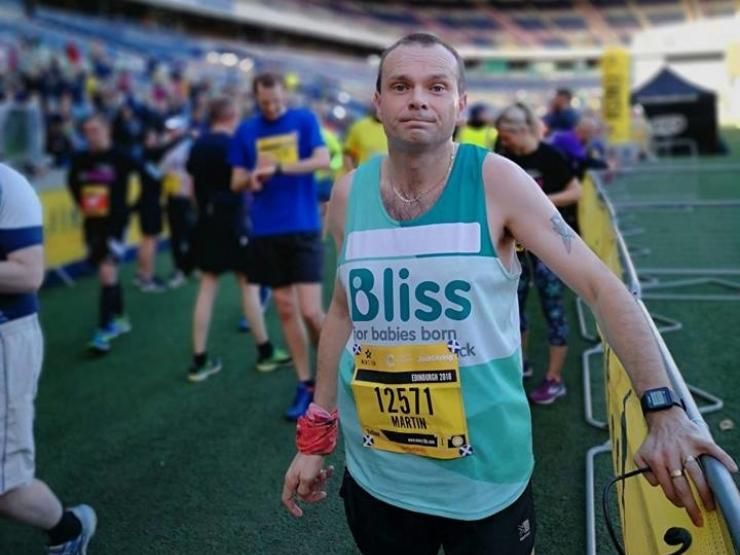 Male in Bliss running vest at men's 10k finish line