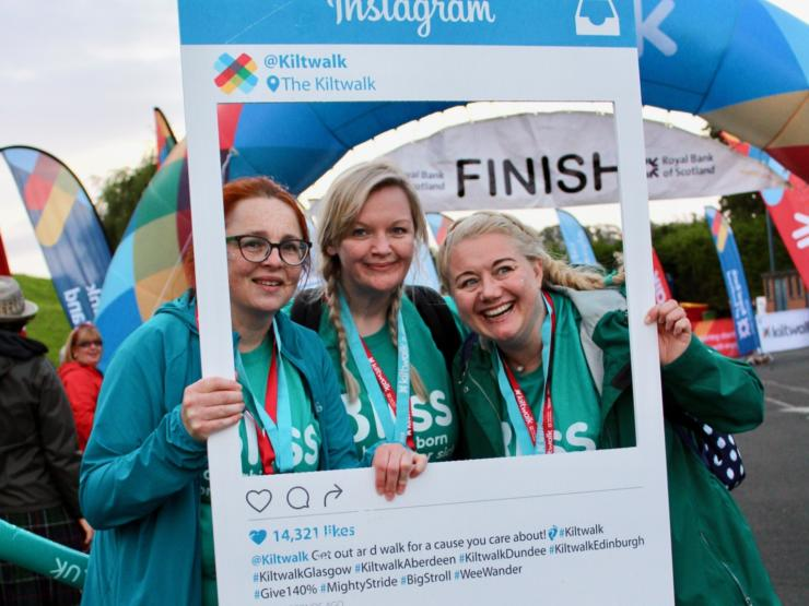 Three women in Bliss t-shirts holding photo frame at finish line