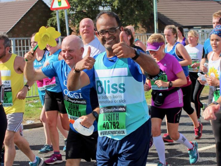 Man wearing glasses giving thumbs up as he runs