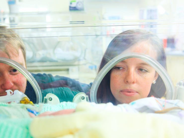 Mum and dad looking into incubator at baby