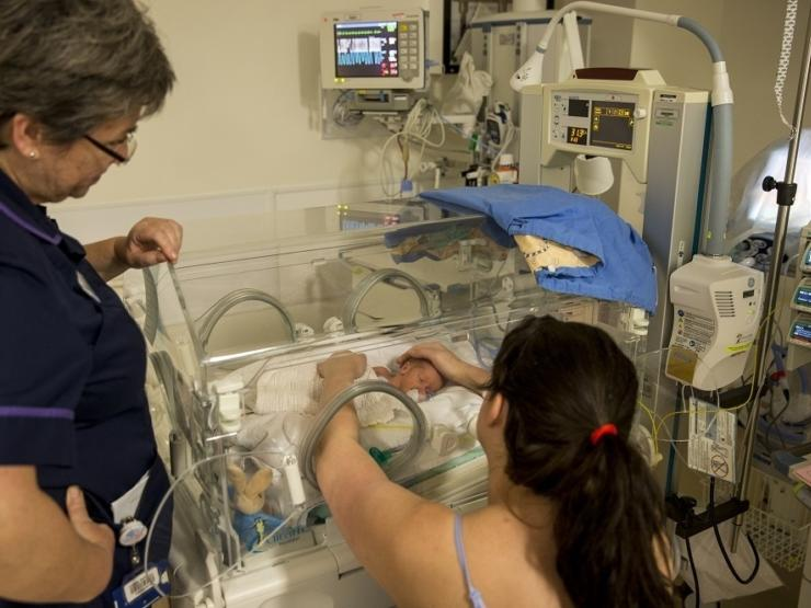 Mum sitting down looking away from the camera reaching into the incubator with both hands, holding her baby and looking at eye level. A nurse is standing next to her looking into the incubator