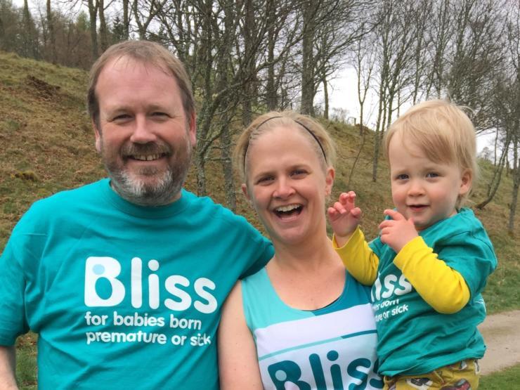 A man in Bliss t-shirt standing next to a female runner in Bliss running vest holding toddler wearing Bliss t-shirt.