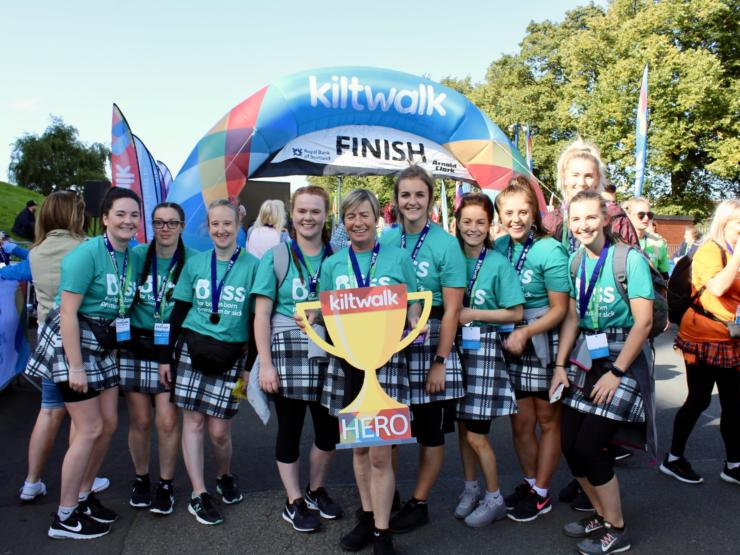 Group of women wearing kilts and bliss t-shirts at Kiltwalk finish line holding foamboard cut-out Kiltwalk hero trophy