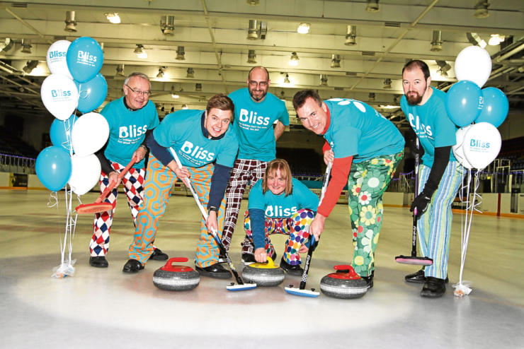 six people in Bliss t-shirts and colourful trousers with their curling equipment and Bliss balloons