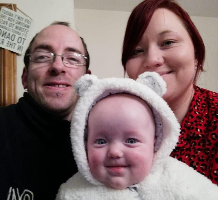 mum, dad and their baby daughter smiling