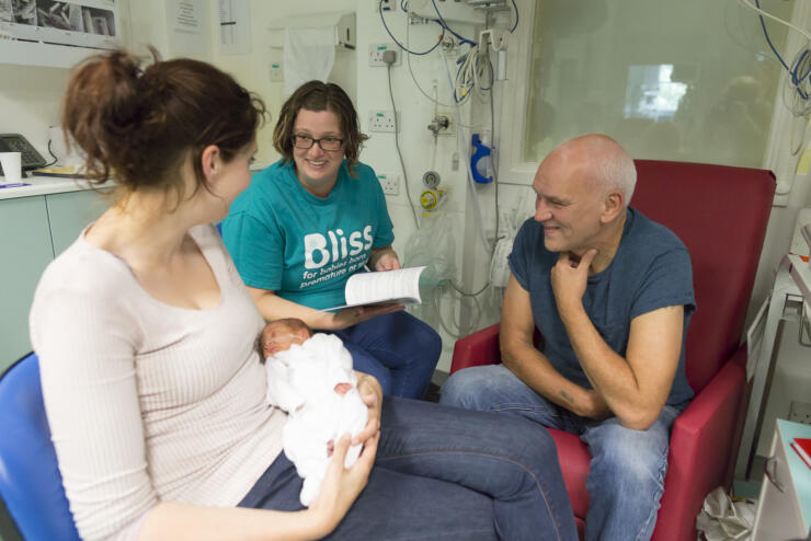 Bliss champion on a unit talking to parents with mum holding the baby