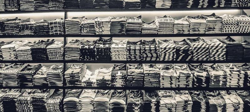 Black and white image of stacked T-shirts