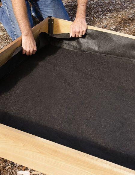 Polypropylene fabric liner being installed inside a cedar raised bed