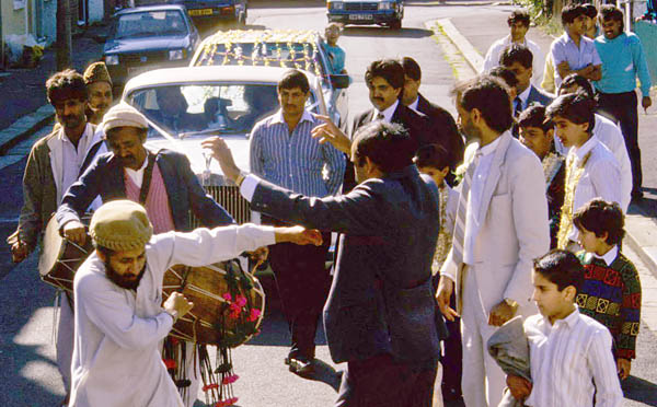 Colour photograph showing a crowd of men and boys on the street.  One is playing a drum and two are dancing.