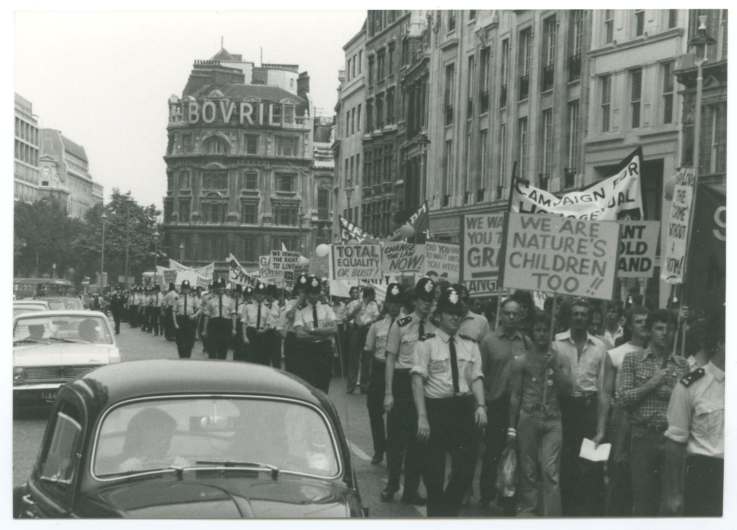 Black and white photo of marchers and police at Gay Pride march, London in 1974