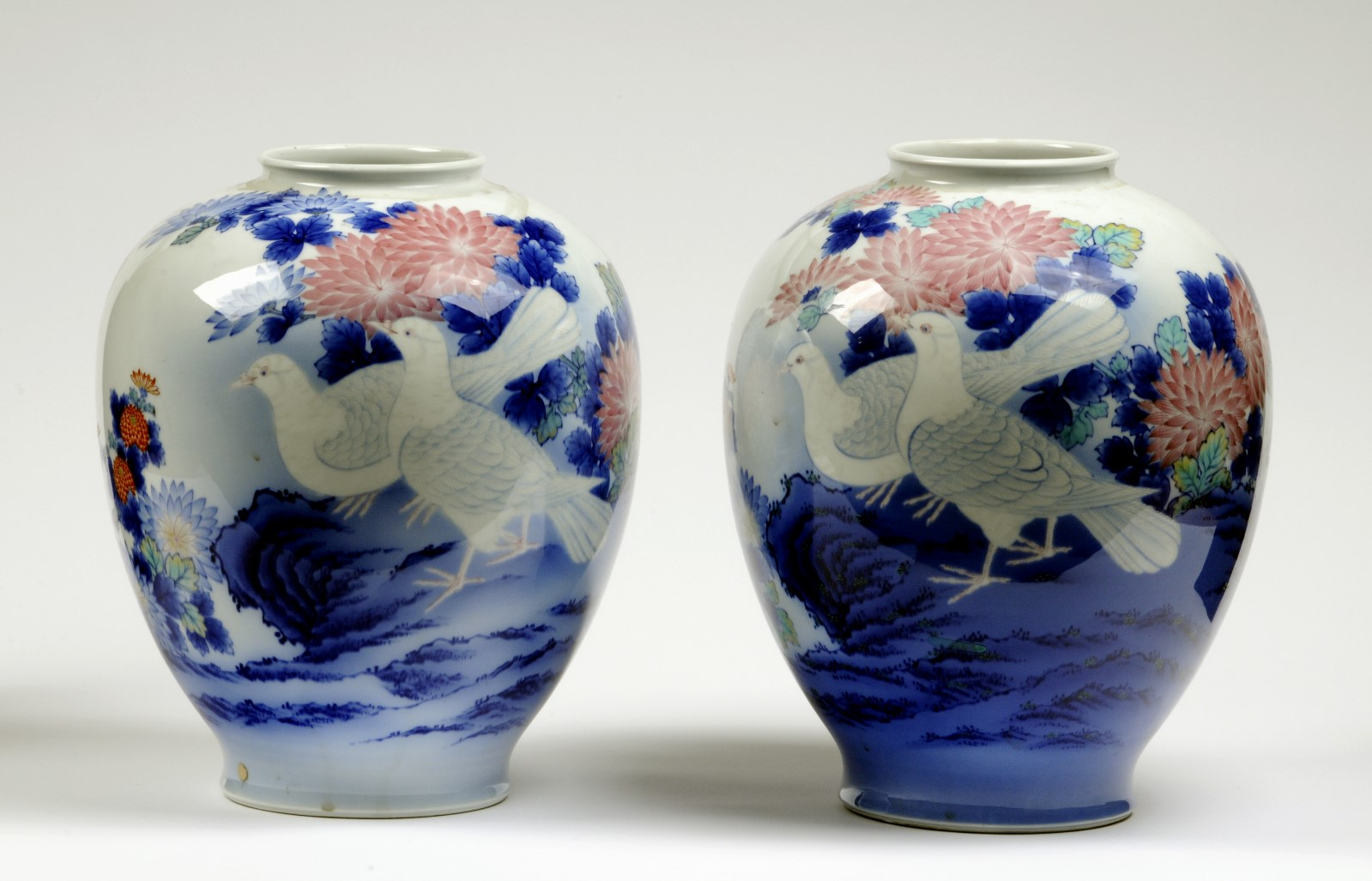 Pair of ceramic vases in white, blue and pink. Two birds on each vase with pink and blue flowers in the background