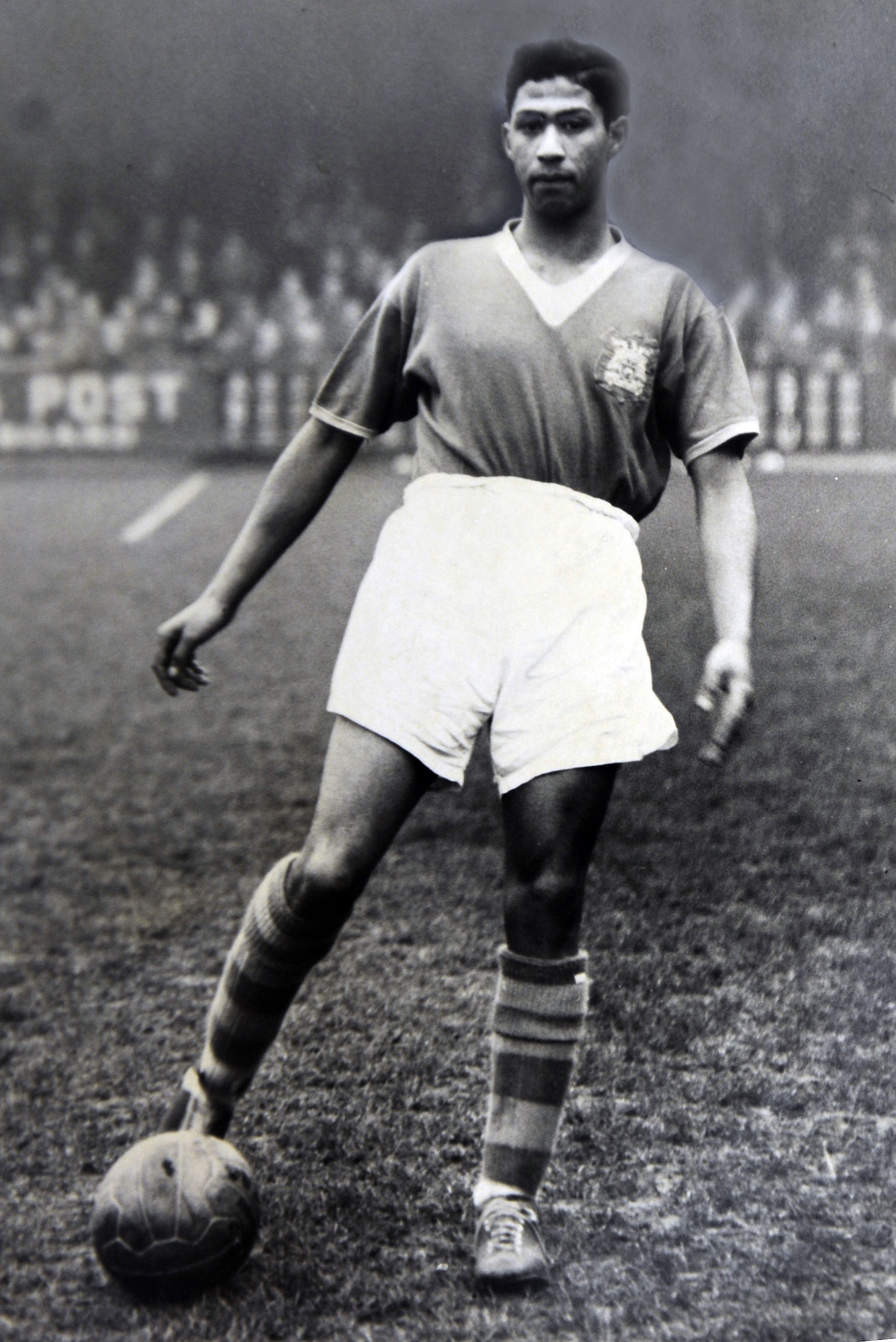 Black and white photograph of Gerry Francis with one foot on a football