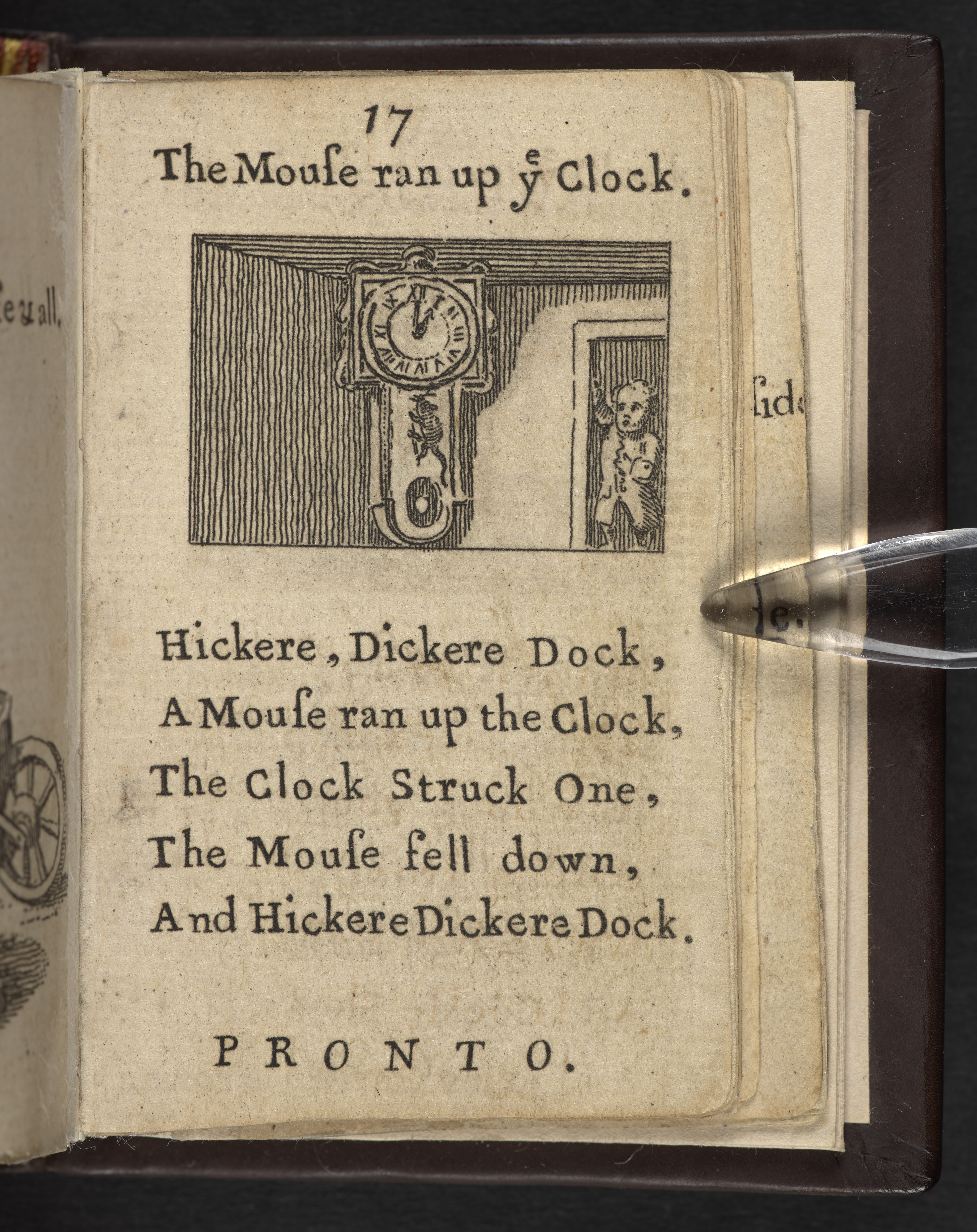 Page from a tiny book with a rhyme printed on it and a picture of a clock and a mouse.