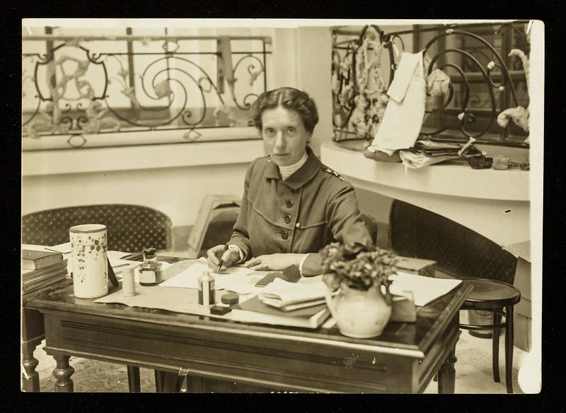 Black and white photo of Flora Murray sitting at her desk