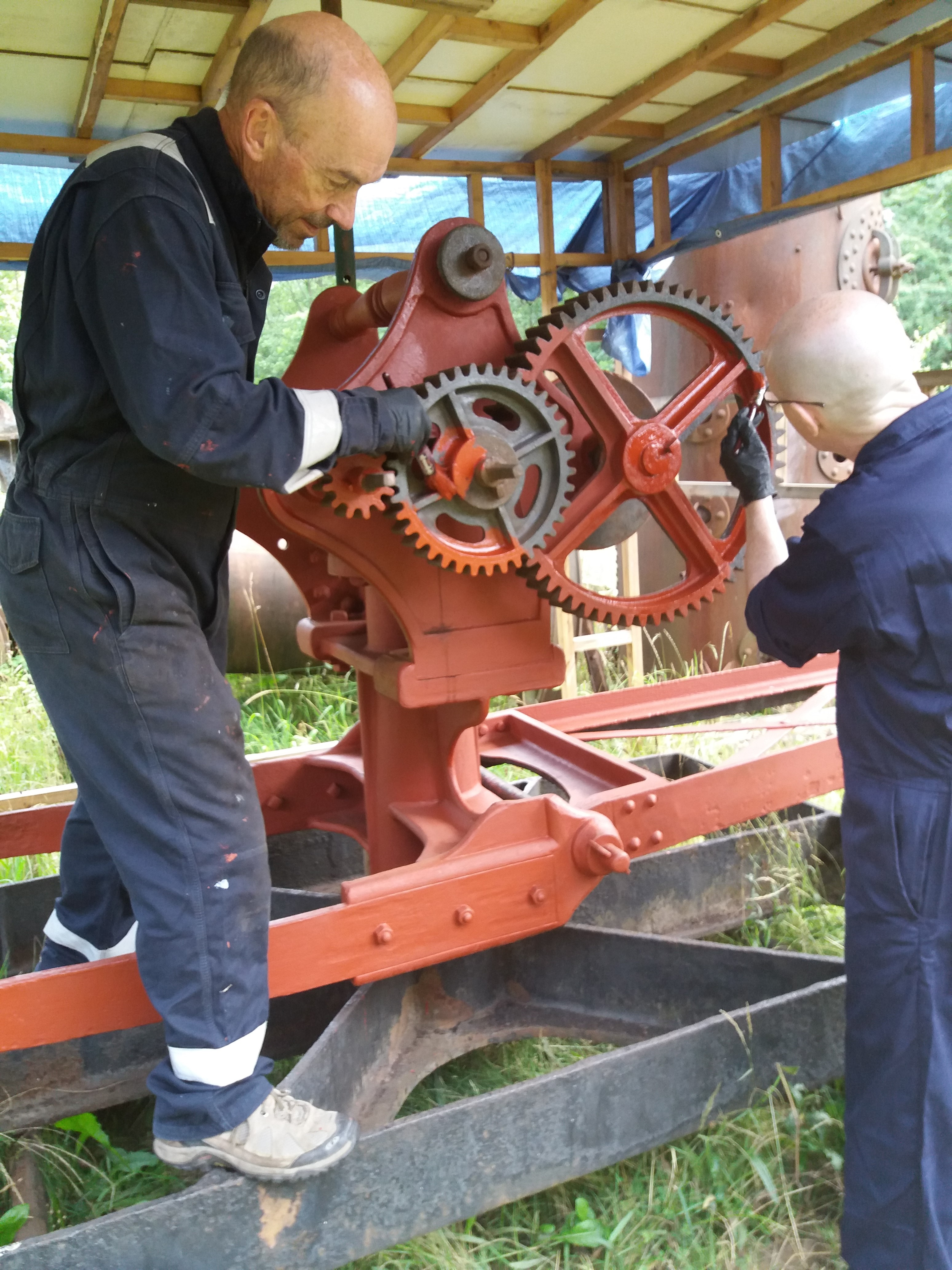 Two men in overalls painting cogs on part of a machine.