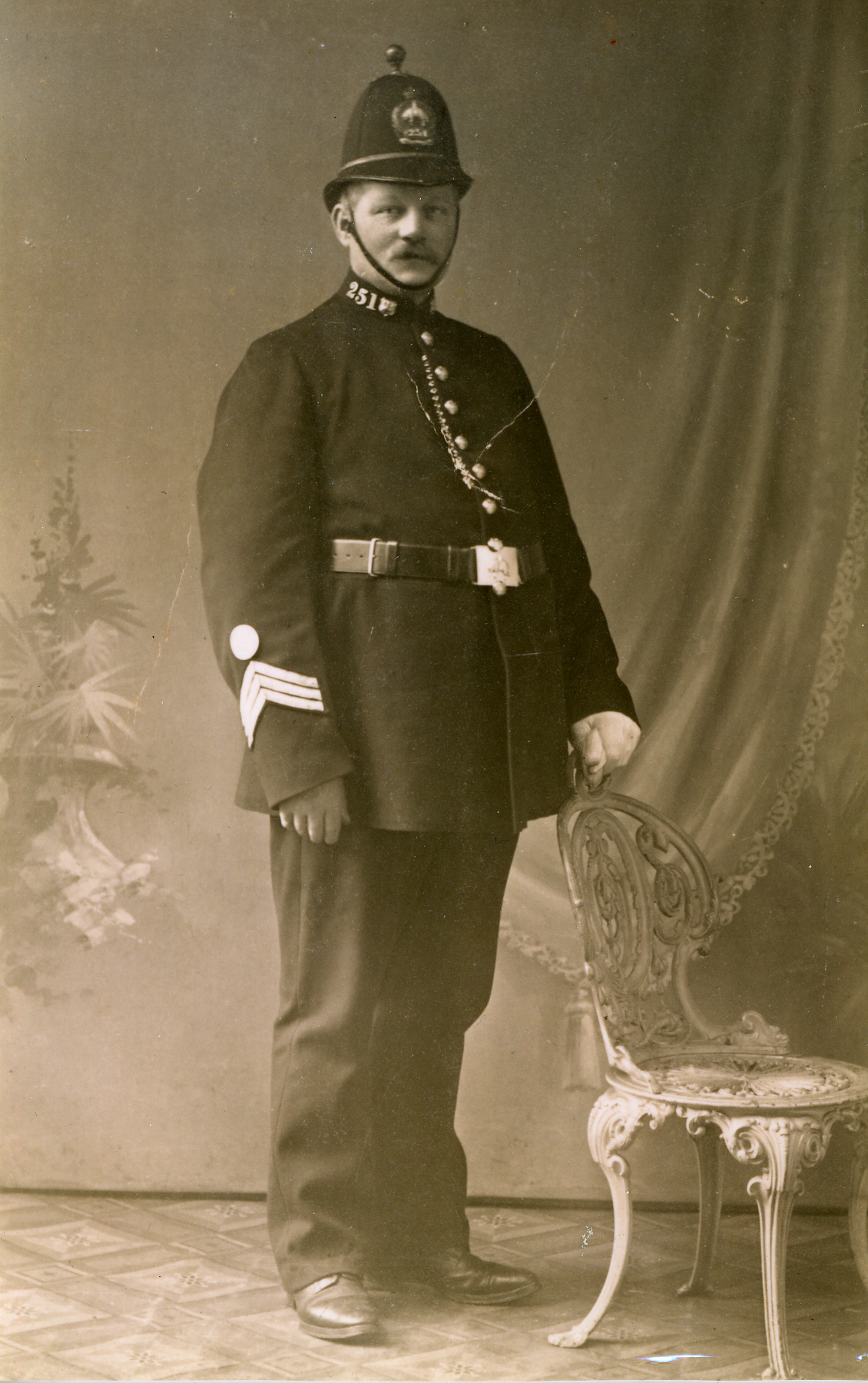 Photograph shows John Horner in police unifrom with a tall helmet.  Three chevrons on his sleeve indicate he is a sergeant.