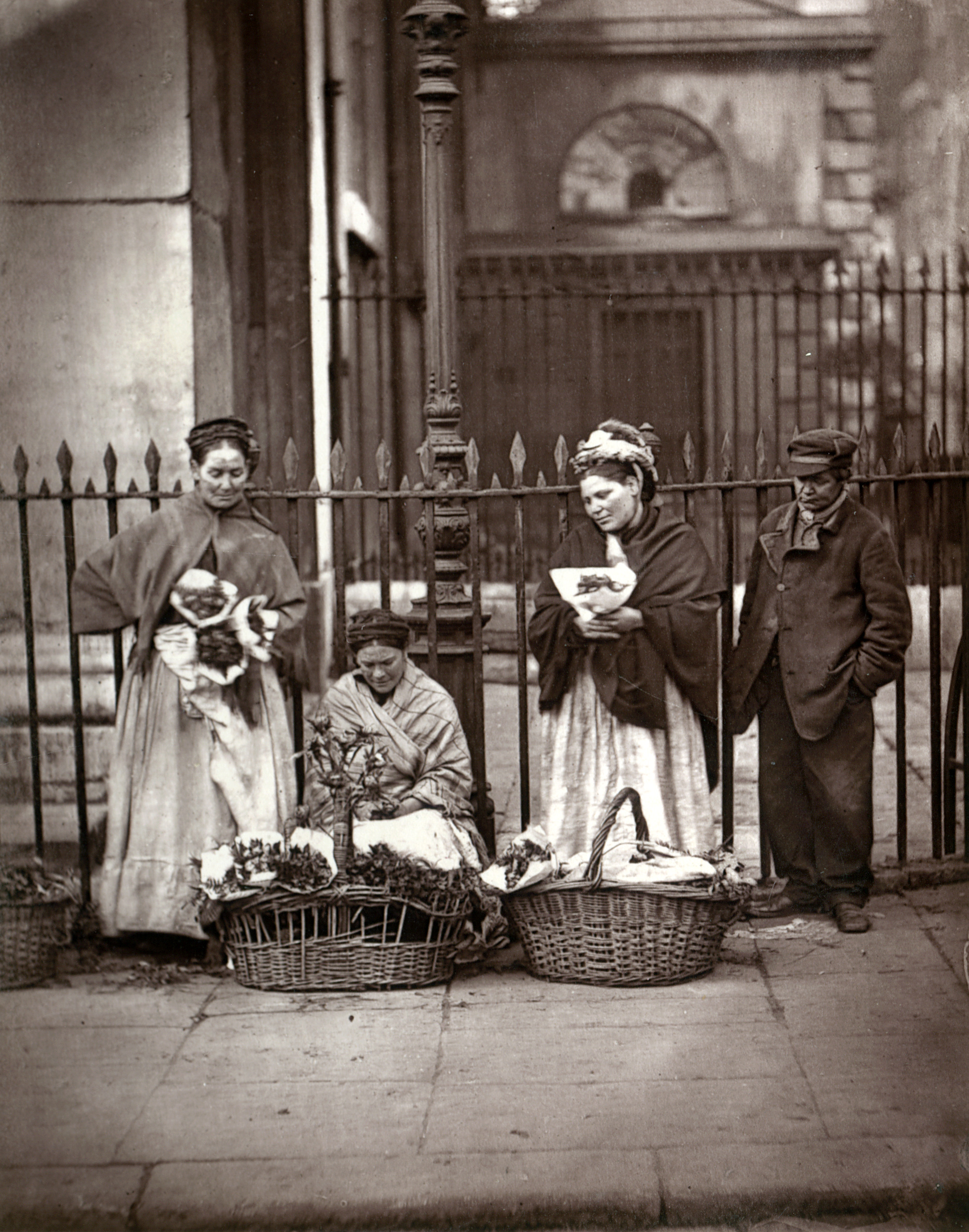 Black and white photograph showing three women with baskets of flowers and a man  in a cap looking on.
