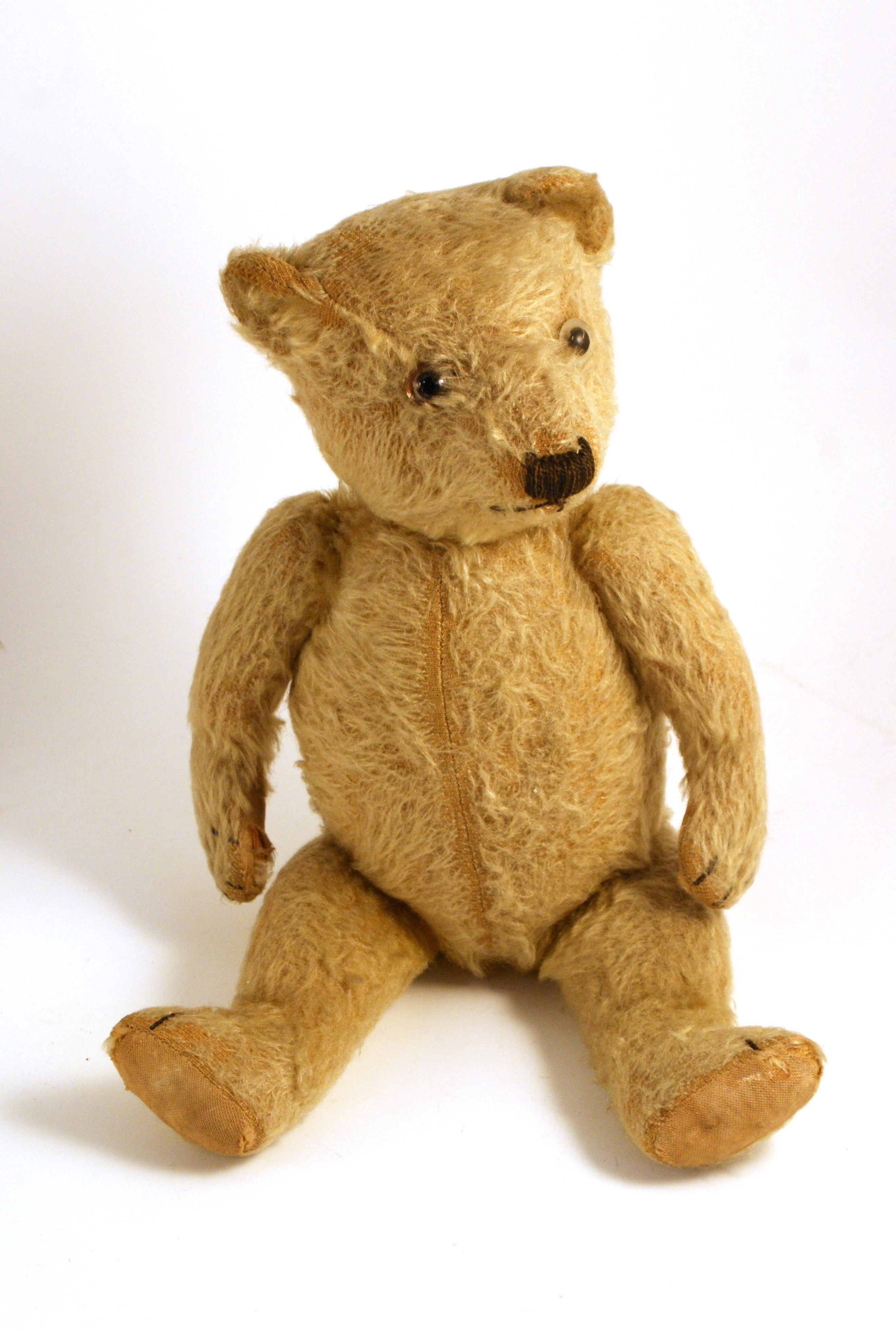 Jointed pale yellow teddy bear with seam down its belly.  It looks well loved.
