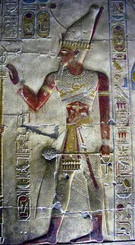 Colour image of an Egyptian carving  of a man holding a staff and surrounded by hieroglyphs