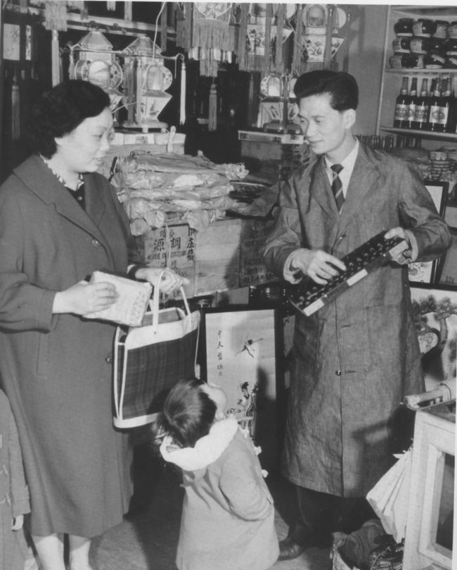 Black and white photograph of a man and a woman in a shop selling Chinese goods.