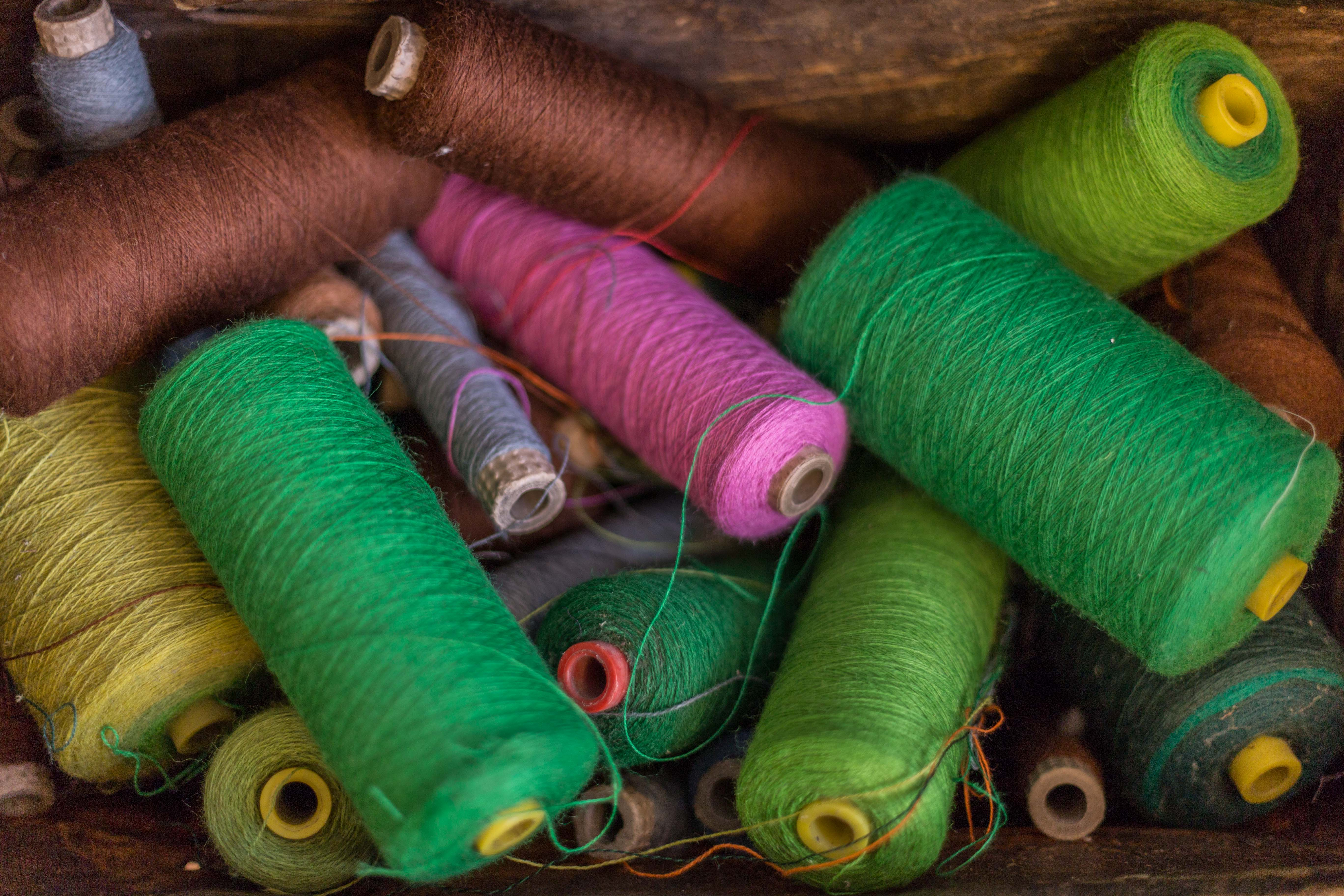 A collection of coloured yarns, including brown, greens, pink and purple