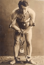 Harry Houdini posing with chains and padlocks wrapped around his body