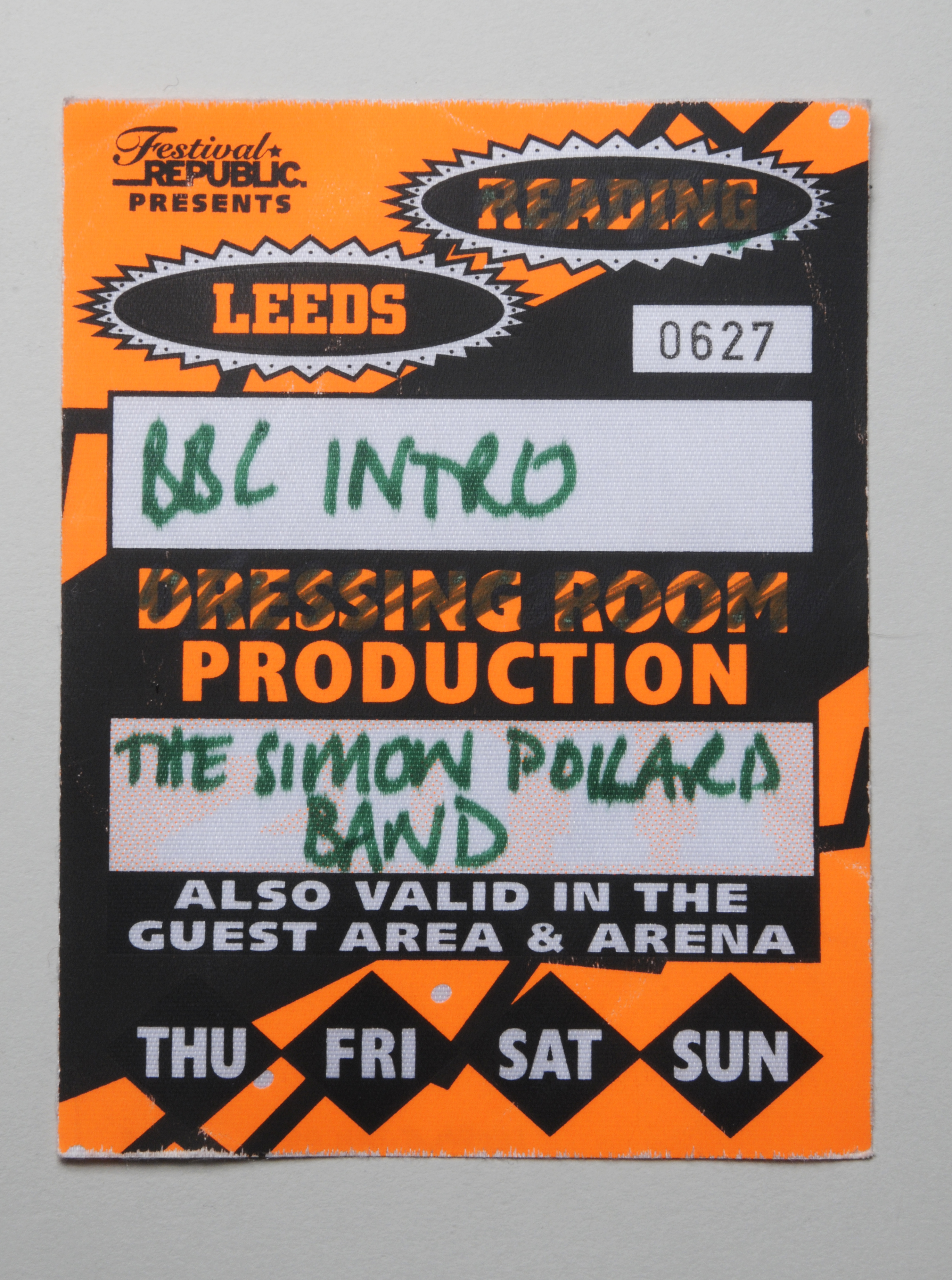 Orange and black print design on thin card.  Pass number 0627 with 'BBC INTRO' and 'Simon Pollard Band' written  on it.