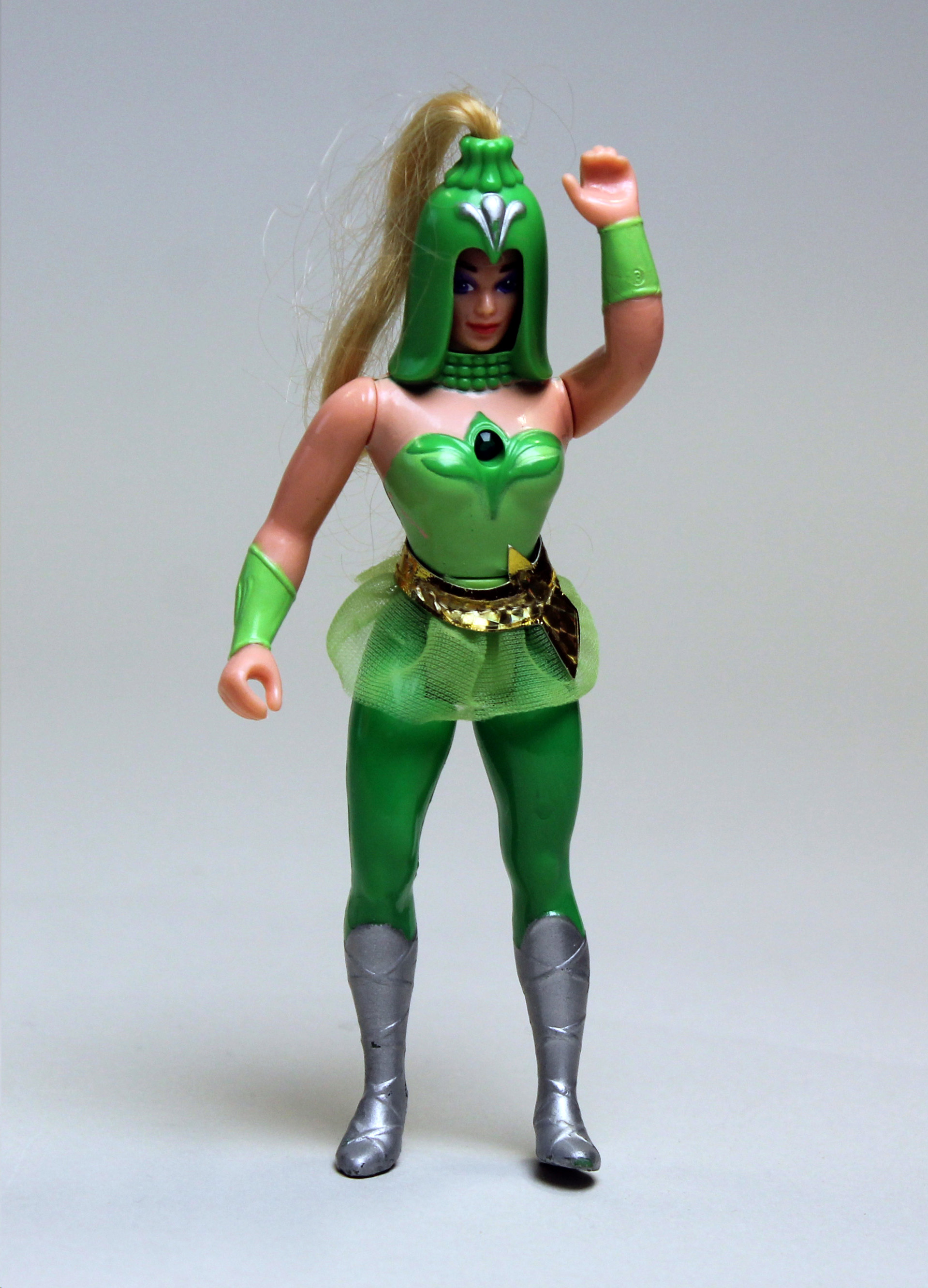 Colour photograph of a figurine of a female character wearing a green costume, including a large, green helmet