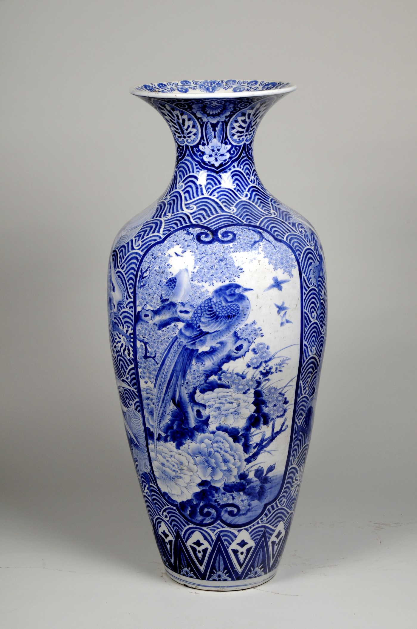 Blue and white ceramic vase with an image of a bird in the centre and wave motifs around it